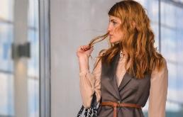 Elegancko ubrana, rudowłosa kobieta, stojąca w przestrzeni biurowej