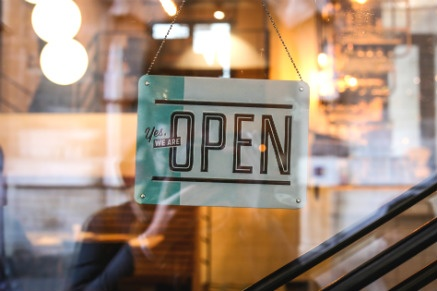Znak wiszący na przeszklonych drzwiach oświetlonego sklepu, mówiący