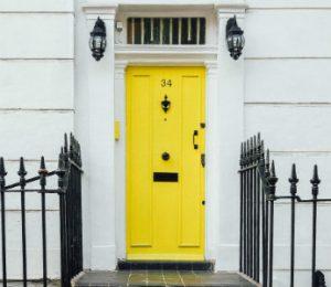 Żółte drzwi wejściowe i czarne schodki prowadzące do białej kamienicy, otoczonej czarnym ogrodzeniem
